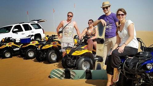 four people sit on ATV's on sand dunes in Dubai