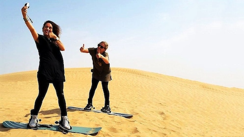 two women taking selfie while on sand boards in Dubai