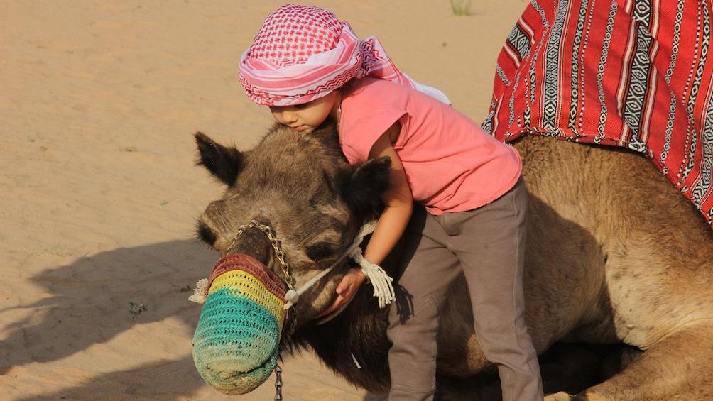 Show item 3 of 10. young boy hugging camel in Dubai