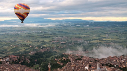 hot air balloon flying over a town in Tuscany