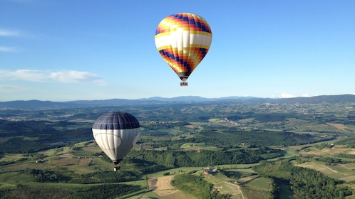 two hot air balloons flying near each other in Tuscany