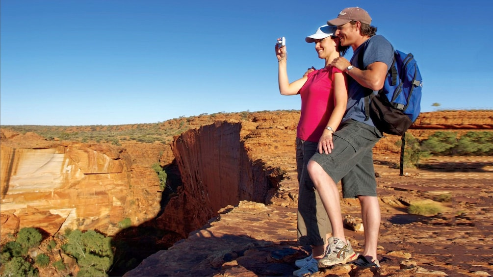 Couple taking a photo from the top of Kings Canyon in Central Australia