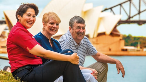 A group of three people sit in front of Sydney Harbour