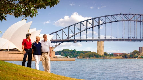 Group of three people stand for a picture in front of the Sydney Opera House and bridge in Sydney