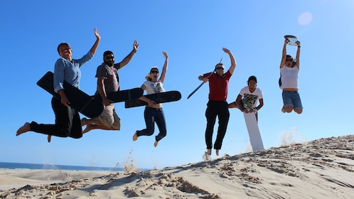 A group jump in the air with their sandboards at Stockton Bight Sand Dunes