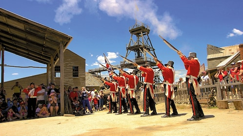 Actors in soldier uniforms firing muskets into the sky in Australia
