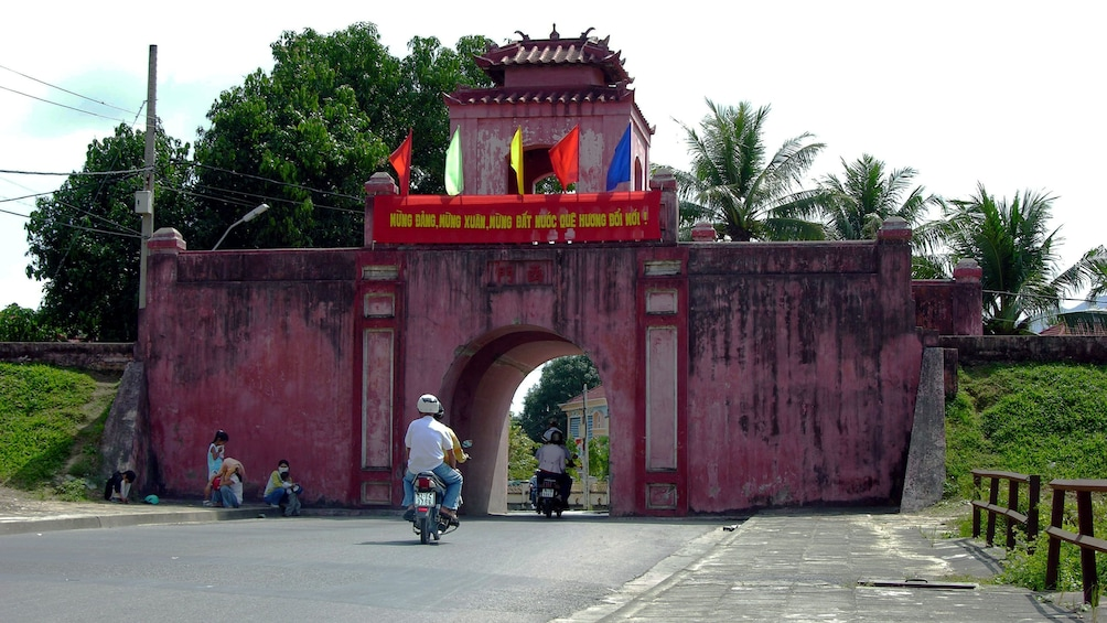 Show item 4 of 9. Riding scooters through a small archway in Nha Trang