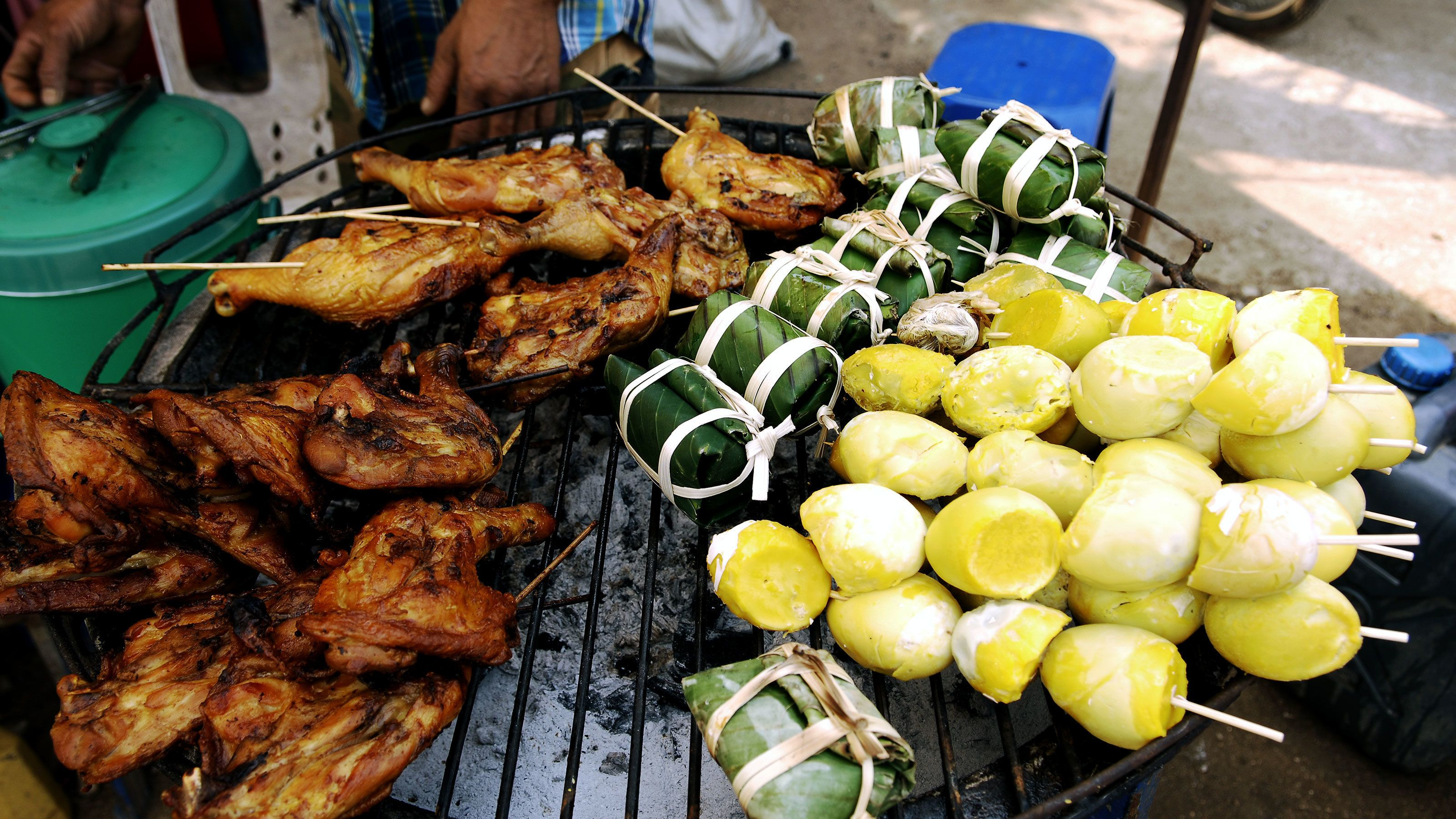 Grilling chicken and vegetables at the market in Bangkok