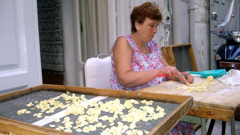 Apri foto 5 di 5. Woman hand cutting and shaping shell pasta in Bari