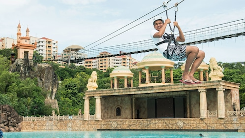 A young man zip lining across a pool at Sunway Lagoon