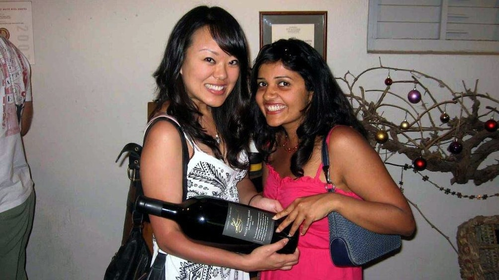 Show item 3 of 8. Pair of women with a large wine bottle at a winery in the Barossa Valley