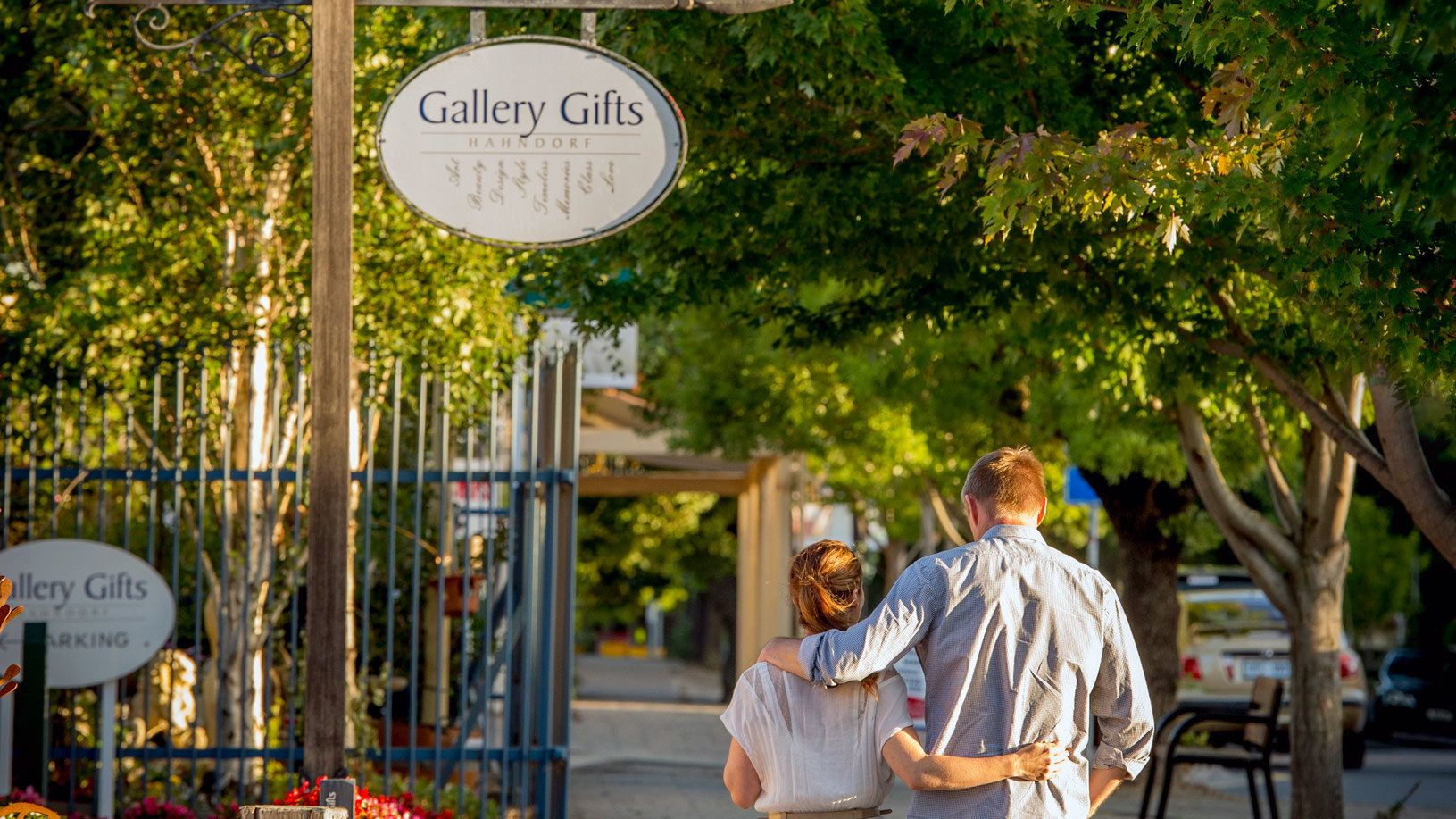 Couple strolling along the tree-lined sidewalk in Hahndorf