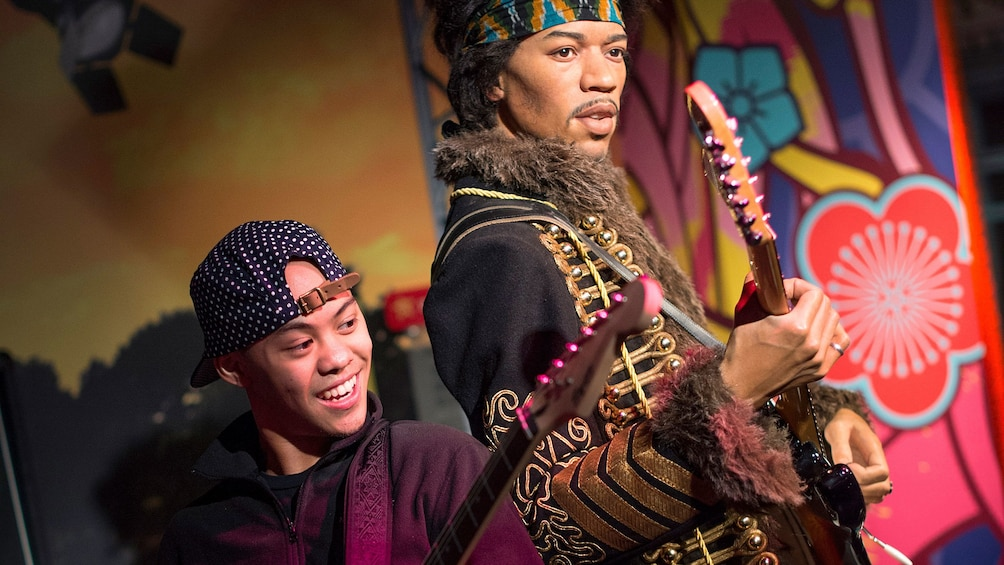 Show item 1 of 10. Boy playing guitar with Jimi Hendrix wax figure at Madam Tussauds in San Francisco