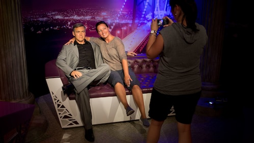 Woman posing with George Clooney wax figure at Madame Tussauds in San Francisco