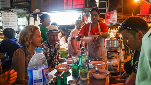 Serving hot street food at the night market in Bangkok