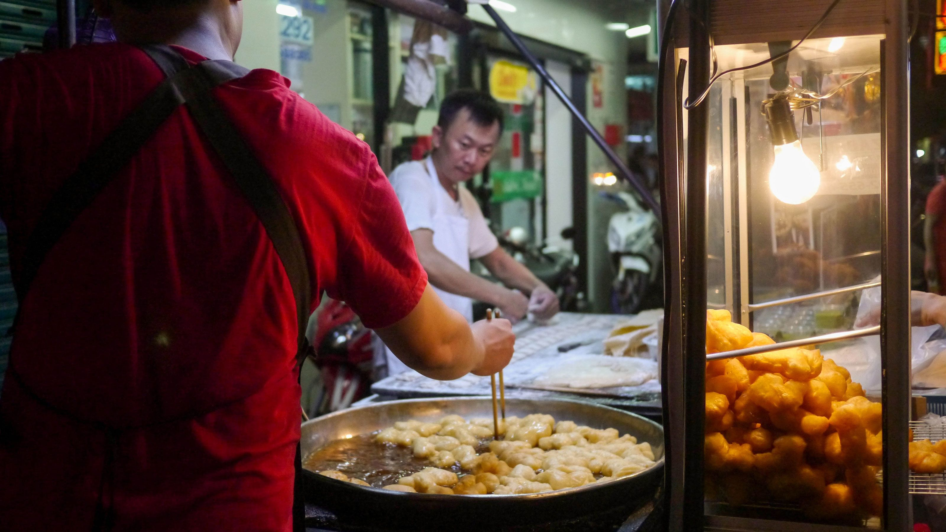 Cooking street food at the night market in Bangkok