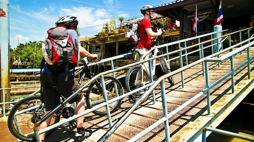 Bicyclists entering a building in the Bangkok countryside.