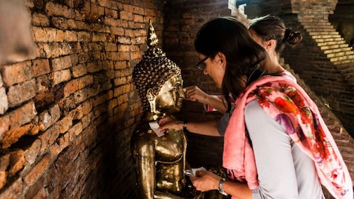Women placing messages with statues in Thailand