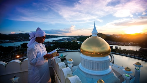 man looking out into the city on top of a mosque in Brunei