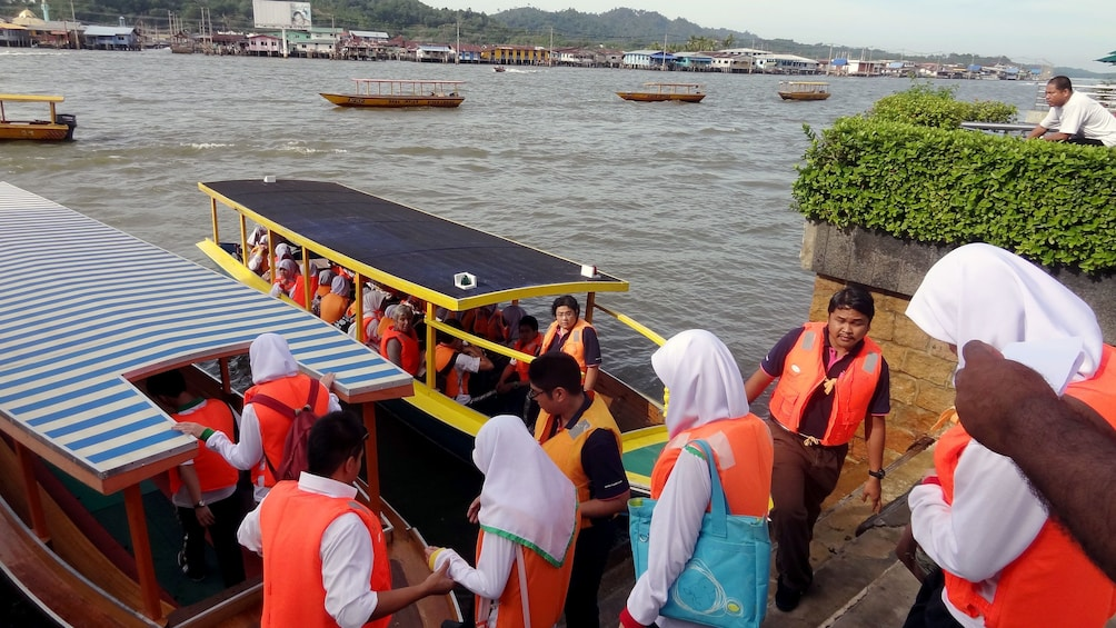 Show item 5 of 5. People getting on a tour boat in Brunei