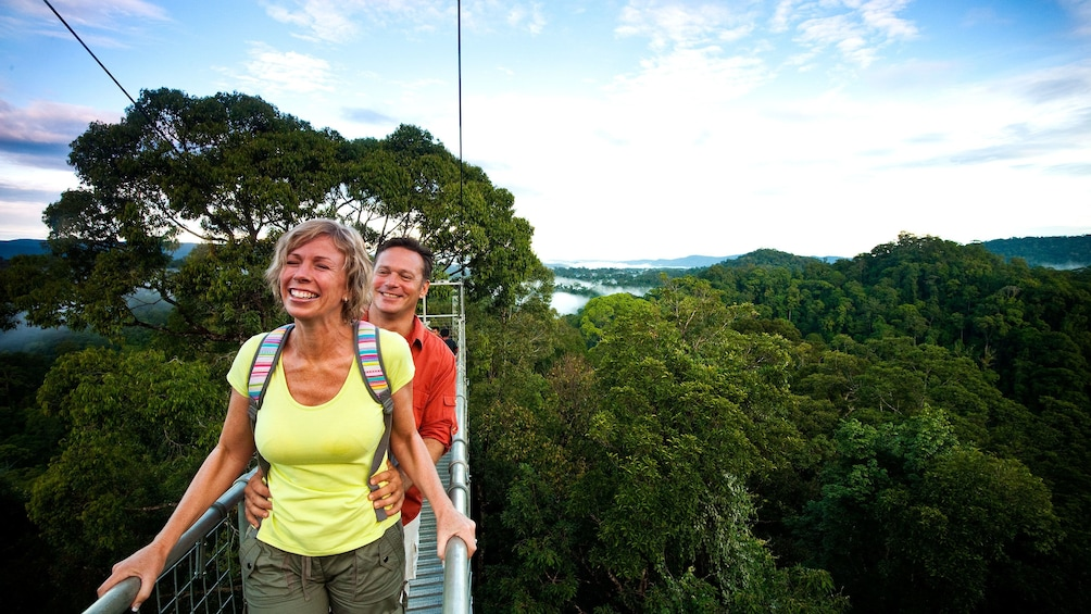 Show item 2 of 5. Couple walking across a suspension bridge at Ulu Temburong National Park