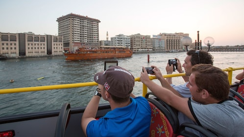 passengers in open air tour bus taking photos of boat in Abu Dhabi