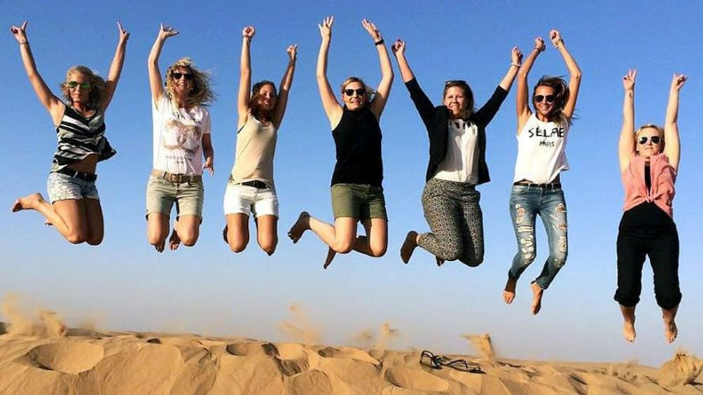 Show item 2 of 8. seven people jumping on sand dune in Abu Dhabi.