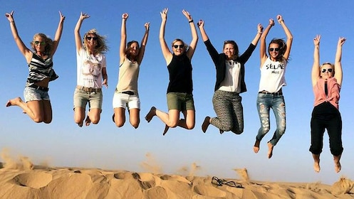 seven people jumping on sand dune in Abu Dhabi.