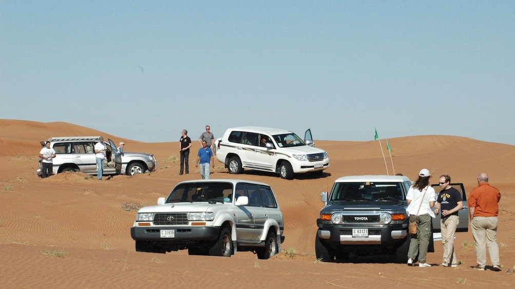 four SUVs and their passengers standing around their vehicles in Abu Dhabi