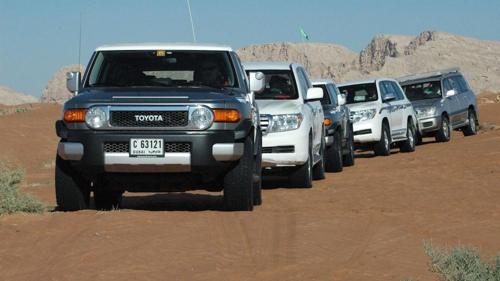 five SUVs driving on sandy ground in Abu Dhabi