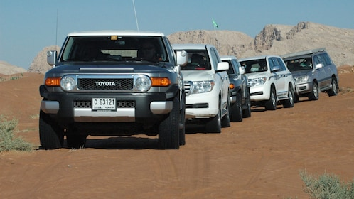 five SUVs driving on sandy ground in Abu Dhabi