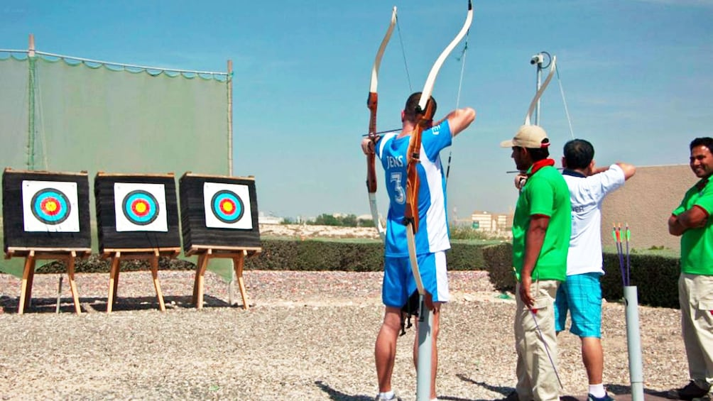 Show item 2 of 5. men at archery competition in Abu Dhabi