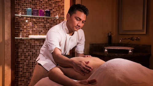 man massaging back of client at spa in Abu Dhabi