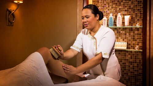 woman exfoliating woman's leg at spa in Abu Dhabi