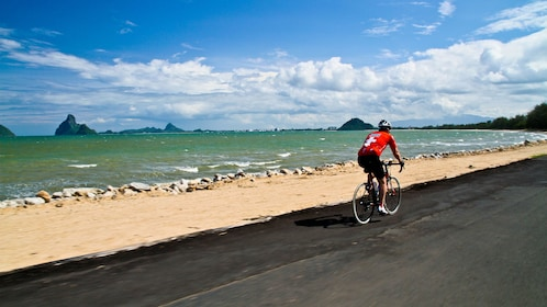 Man cycling along the beach in Bangkok