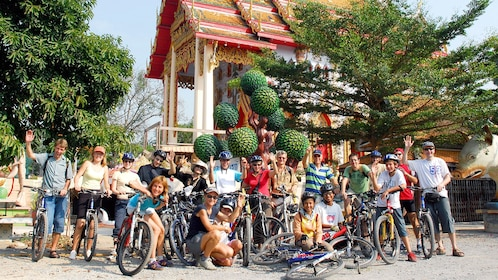 Group of bikers posing in front of a small temple in Bangkok