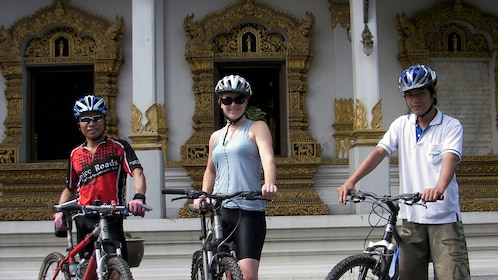 Three bicyclists pose with their bikes in front of a building in Lamphun Thailand