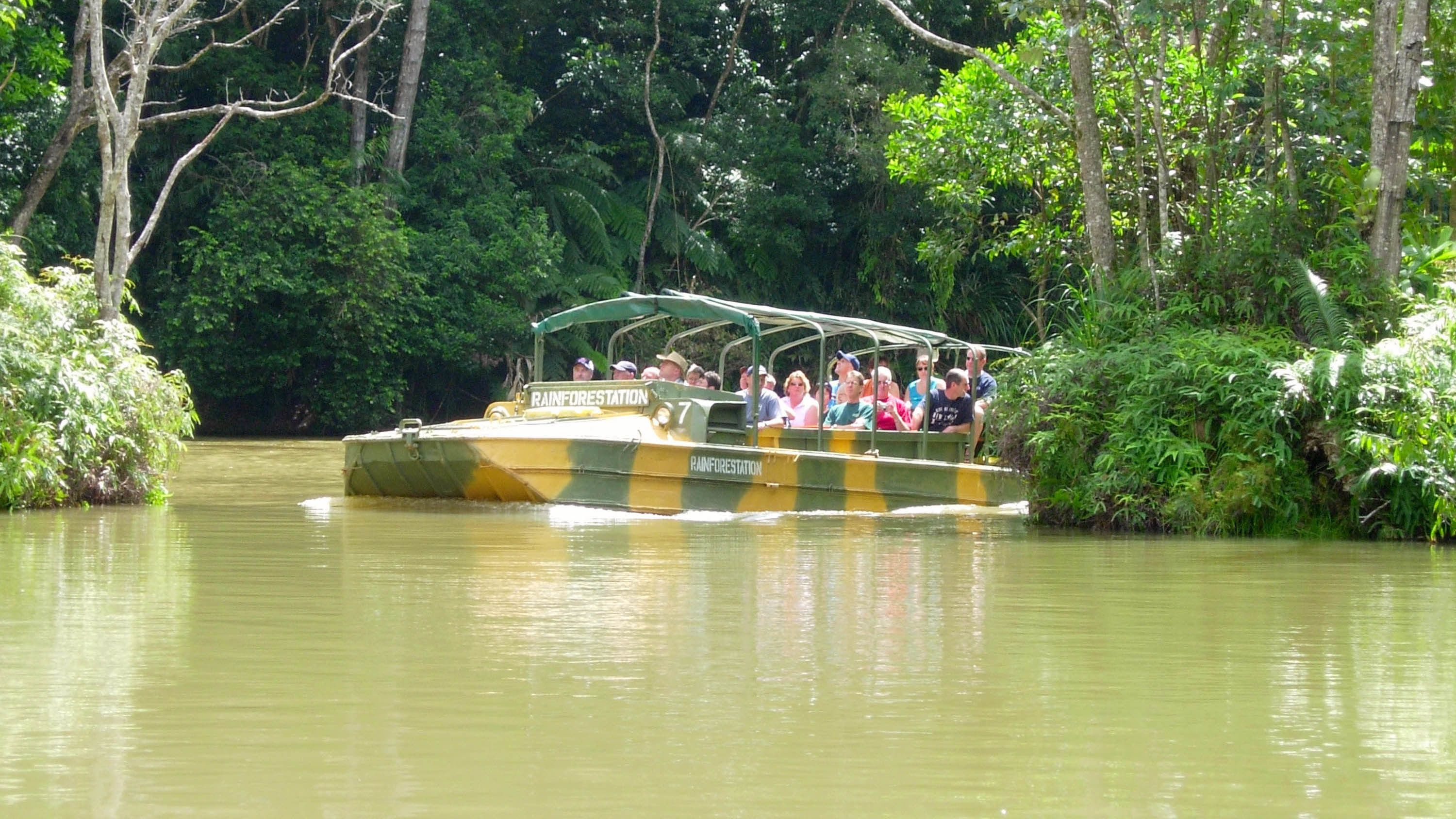 Tourists gliding down the water while they tour the forest in a duck boat in Kuranda