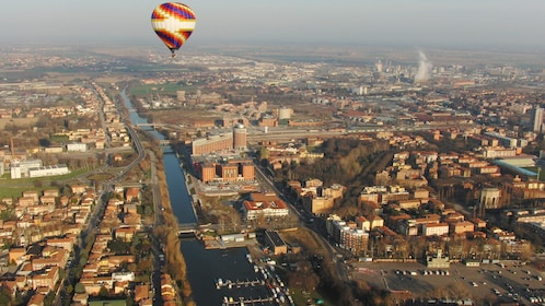 A hot air balloon floating over medieval cities