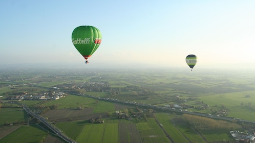 Two hot air balloons hover over green tuscan landscapes