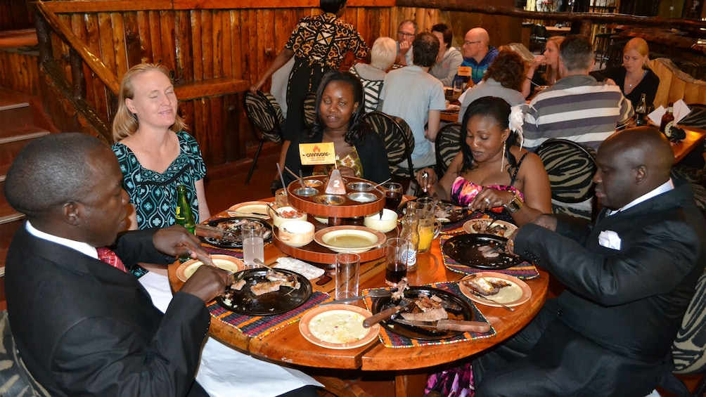 Show item 3 of 4. People sitting and enjoying a meal in Nairobi