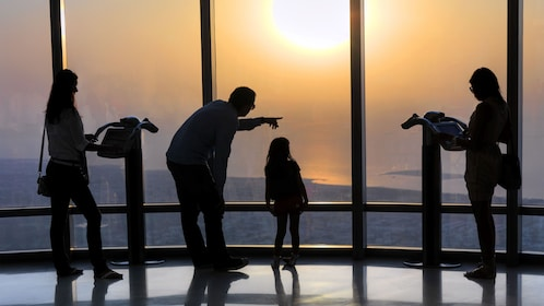 Family silhouetted at the observation deck at the Burj Khalifa at sunset in Dubai