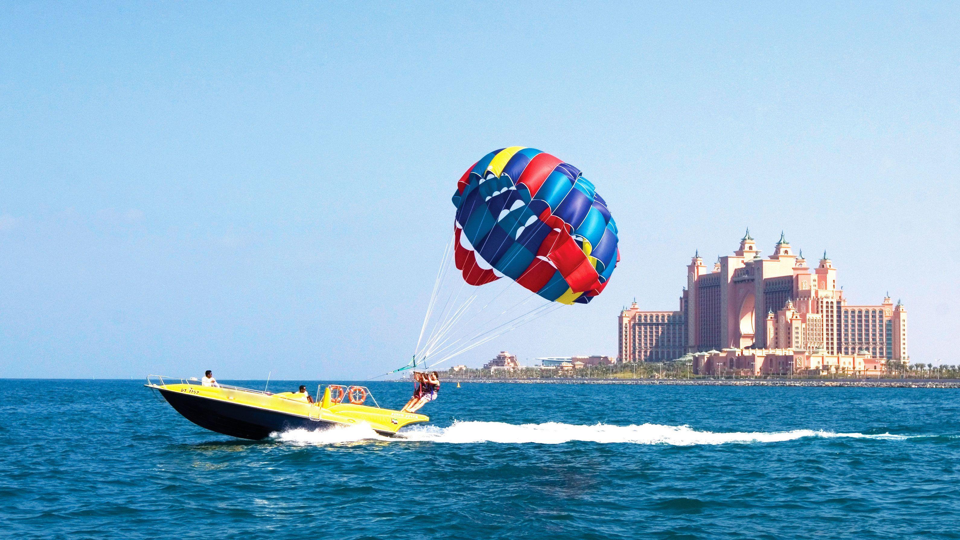 Jet boat with parasailers zipping past Atlantis Resort in Dubai