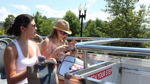 Pair of women on the upper deck of a Hop-On Hop-Off bus in Washington DC