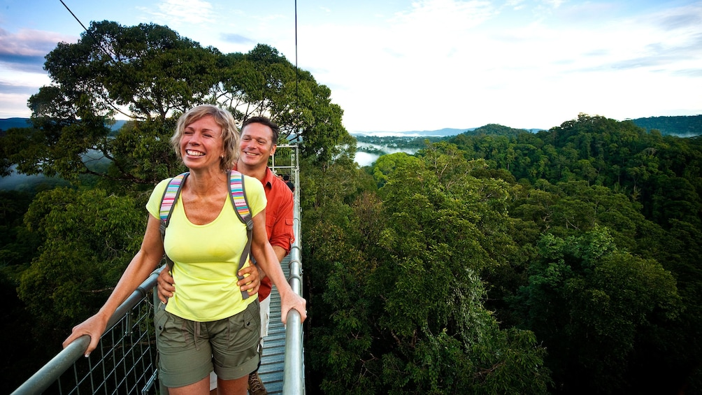Show item 2 of 5. Couple enjoying the beautiful view of Ulu Temburong National Park on a suspension bridge
