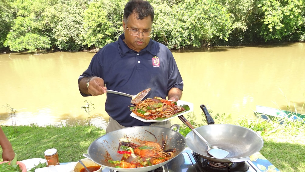 Show item 3 of 5. Man cooking meal at Ulu Temburong National Park for the tourists