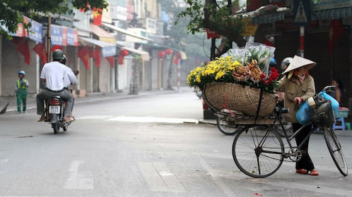 woman carrying a big basket of flowers on her bike in Vietnam