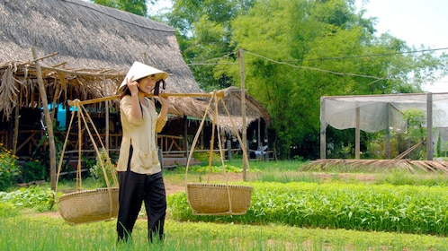 View of a woman carrying baskets of veggies and herbs from the vegetable & herb-growing village of Tra Que in Vietnam