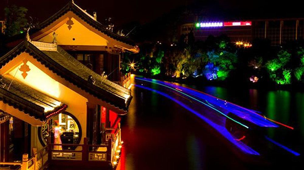 boat passing a structure along the river in Guilin
