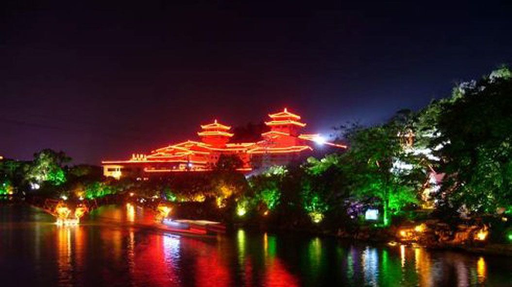 brightly lit buildings along the river in Guilin